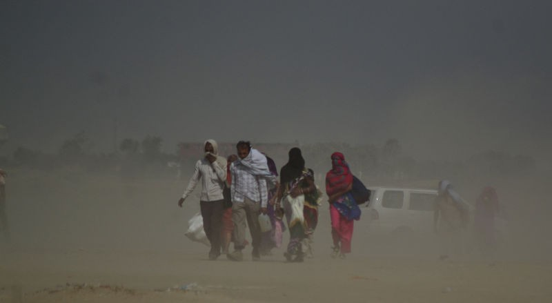 Indian people walk at holy sangam during duststorm in a hot day in Allahabad. Image by Ritesh Shukla. Copyright Demotix (28/5/2015)