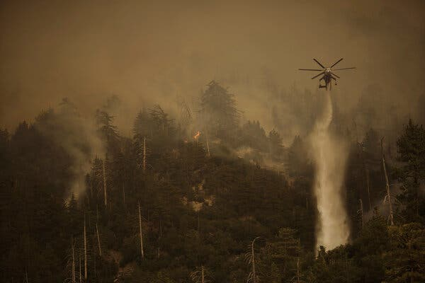 A helicopter in Angelus Oaks, Calif., dropped water on the El Dorado Fire in September.