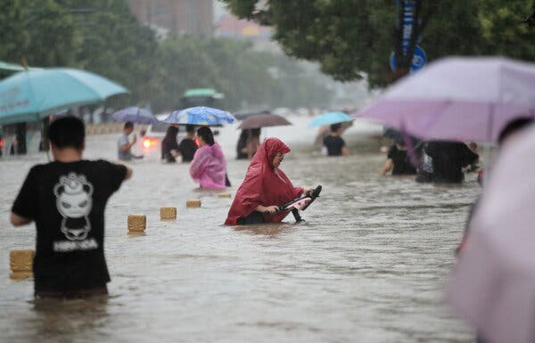 Residents waded through a flooded road amid heavy rainfall in Zhengzhou, China, on Tuesday.