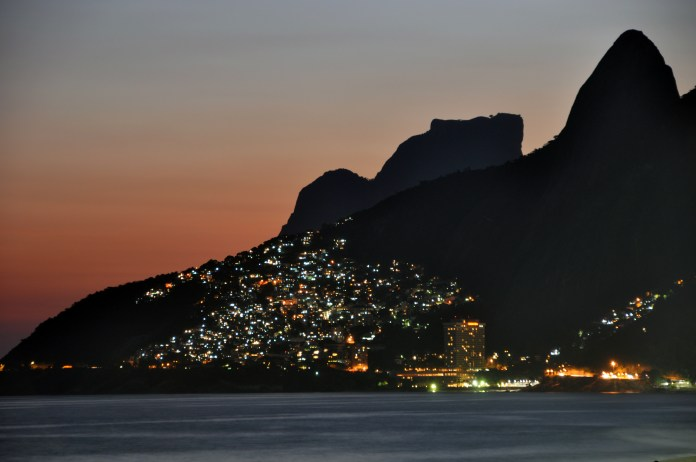 The lights of Vidigal favela in Rio de Janeiro as seen from Ipanema and Leblon beaches. The cone spire to the far right is part of the famous Dois Irmãos.
