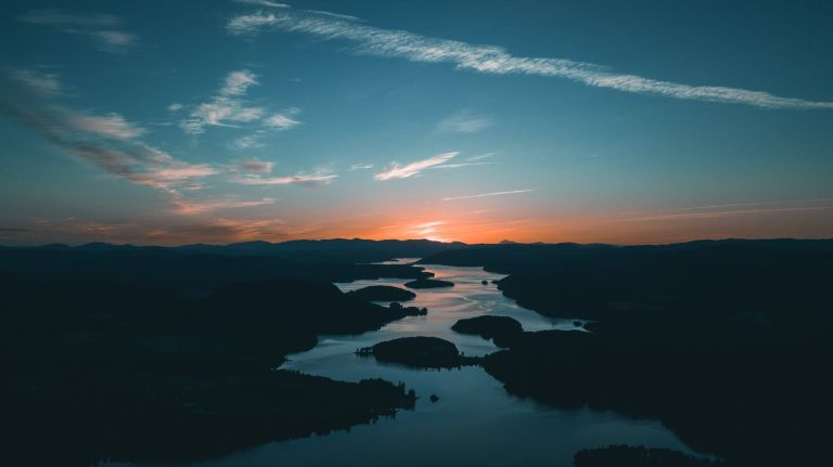 aerial photography of water beside forest during golden hour