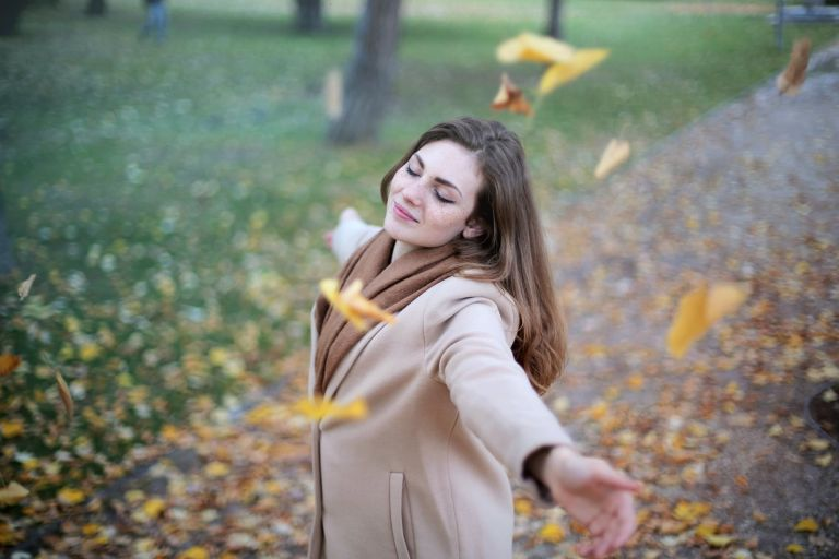 woman open arms while closed eyes smiling photo