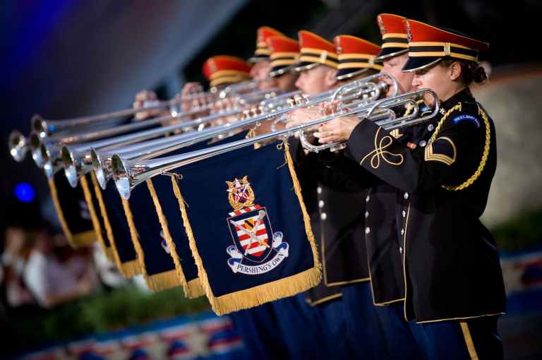 people in uniform using a trumpet instrument with blue and yellow flag under
