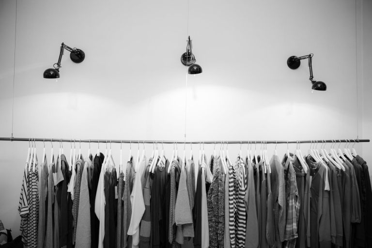 grayscale photography of assorted shirts hanged on clothes rack