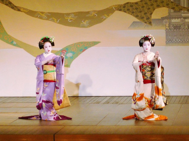 Two maiko dance during a formal performance.