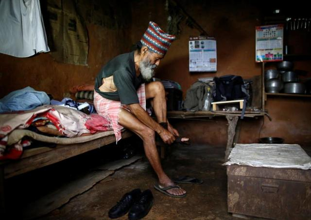 """Durga Kami, 68, who is currently studying in the tenth grade at Shree Kala Bhairab Higher Secondary School, puts on a torn sock and t-shirt, as he gets ready for school in Syangja, Nepal, June 5, 2016. REUTERS/Navesh Chitrakar. SEARCH """"DURGA KAMI"""" FOR THIS STORY. SEARCH """"THE WIDER IMAGE"""" FOR ALL STORIES"""
