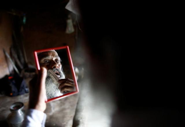 """Durga Kami, 68, who is currently studying tenth grade at Shree Kala Bhairab Higher Secondary School, looks into a mirror as he combs his beard while getting ready for school in Syangja, Nepal, June 5, 2016. Kami has promised his classmate Sagar Thapa that he will cut his beard off if he passes tenth grade. REUTERS/Navesh Chitrakar. SEARCH """"DURGA KAMI"""" FOR THIS STORY. SEARCH """"THE WIDER IMAGE"""" FOR ALL STORIES"""