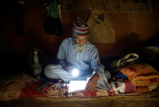 """Durga Kami, 68, who is studying in the tenth grade at Shree Kala Bhairab Higher Secondary School, uses a torch to read a book during a power cut, at his one-room house in Syangja, Nepal, June 4, 2016. REUTERS/Navesh Chitrakar. SEARCH """"DURGA KAMI"""" FOR THIS STORY. SEARCH """"THE WIDER IMAGE"""" FOR ALL STORIES"""