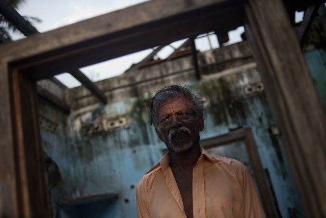 Anthony Fernando, a Tamil civilian, stands at the entrance of his house in the Mullaitivu district, which was badly damaged during the fighting. His wife and daughter were killed during the war.