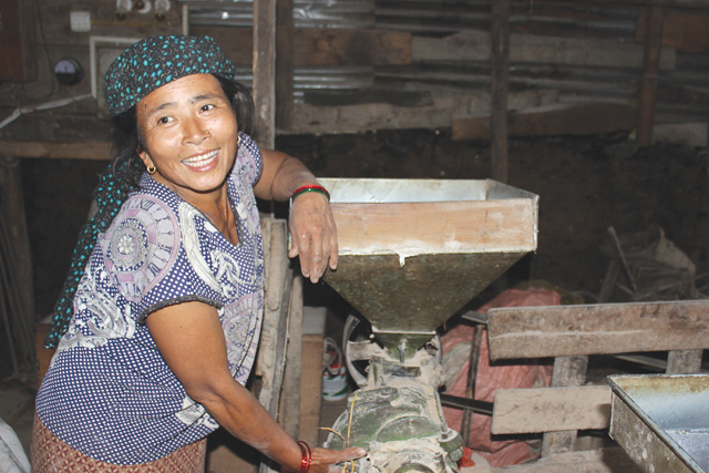 Gami Ghale runs a rice huller, a flour mill and an oil extractor from her shed, a temporary structure made of green corrugated tin sheets.