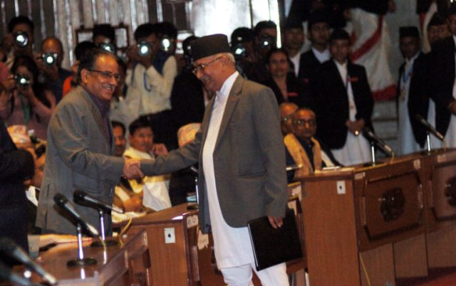PM KP Sharma Oli shakes hands with CPN Maoist Centre Chairman Pushpa Kamal Dahal after announcing his resignation at the Parliament, on Sunday, July 24, 2016.