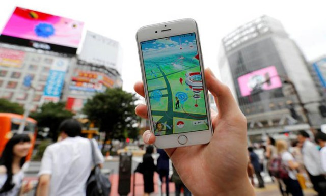 "A man poses with his mobile phone displaying the augmented reality mobile game ""Pokemon Go"" by Nintendo in front of a busy crossing in Shibuya district in Tokyo, Japan, July 22, 2016. REUTERS/Toru Hanai"
