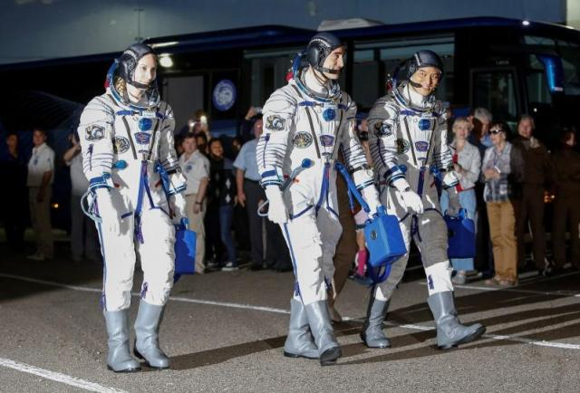 The International Space Station (ISS) crew members (L to R) Kate Rubins of the U.S., Anatoly Ivanishin of Russia and Takuya Onishi of Japan walk after donning space suits at the Baikonur cosmodrome, Kazakhstan, July 7, 2016. REUTERS/Shamil Zhumatov