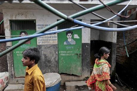 In this June 1, 2016 photo, Bangladeshis walk past a public toilet in a slum area in Dhaka, Bangladesh. Bangladesh's overpopulated urban areas are proving to be more of a challenge in the campaign for sanitation, mostly because the opportunity for contaminating water supply is much higher.