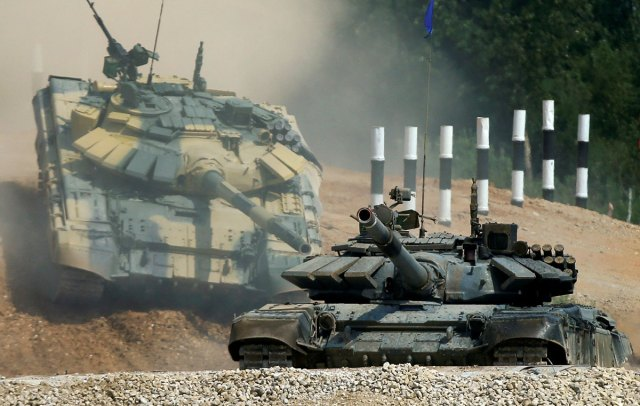 T-72 tanks, operated by crews from Kuwait (front) and Nicaragua, drive during the Tank Biathlon competition, at a range in the village of Alabino outside Moscow.
