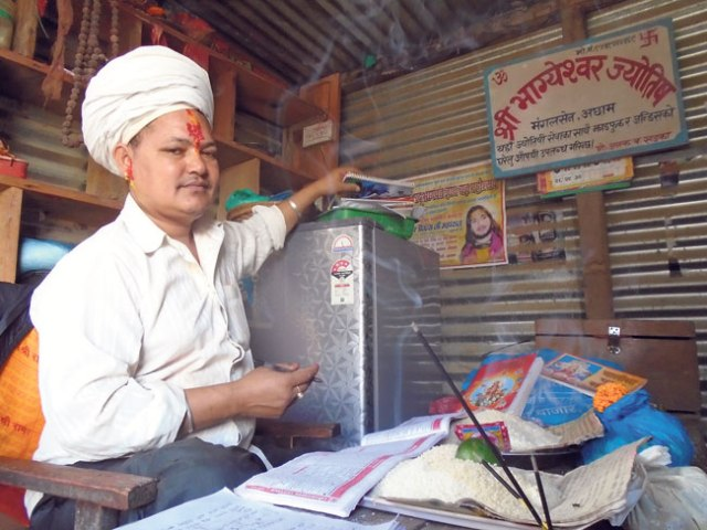 46-year-old Janak Bahadur Khadka, a local religious leader, waits for clients in his shop. (Binita)