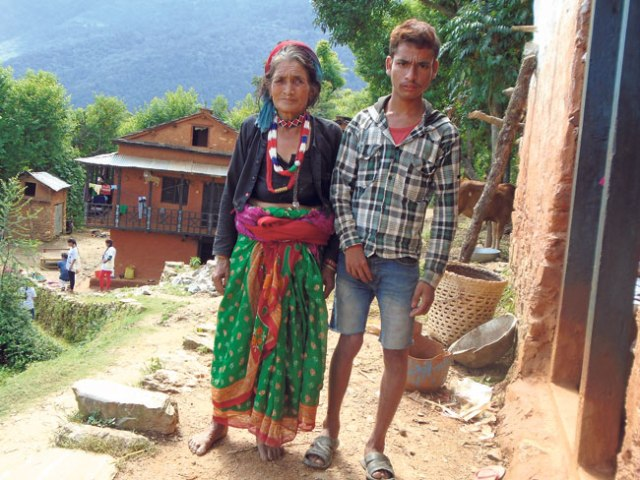 A differently abled mother and son stand outside their home in Mangalsen of Achham. (Neelam)