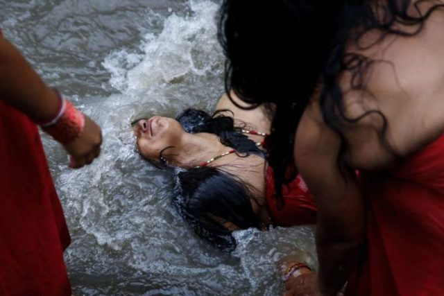 A Nepalese Hindu woman dips in the Bagmati River to purify herself inside Pashupathinath Temple premise, a UNESCO World Heritage Site in Kathmandu, Nepal on Tuesday, September 6, 16. Rishi Panchami is observed to mark the end of three-day Teej festival when women worship Sapta Rishi (Seven Saints) on the last day to wash off one's impurity for the whole year.