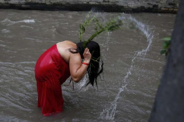 A Nepalese Hindu woman takes a ritual bath lashing with leaves of the Aghada plant that is considered sacred during Rishi Panchami festival on the banks of Bagmati River inside Pashupathinath Temple premise, a UNESCO World Heritage Site in Kathmandu, Nepal on Tuesday, September 6, 16. Rishi Panchami is observed to mark the end of three-day Teej festival when women worship Sapta Rishi (Seven Saints) on the last day to wash off one's impurity for the whole year.