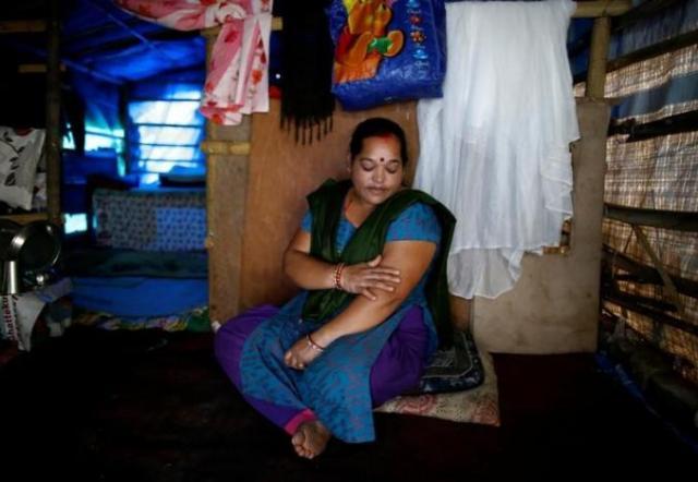 Shanti Pariyar, 42, sits inside her makeshift shelter as she speaks during an interview at Chuchepati in Kathmandu, Nepal, September 19, 2016. Thomson Reuters Foundation/Navesh Chitrakar