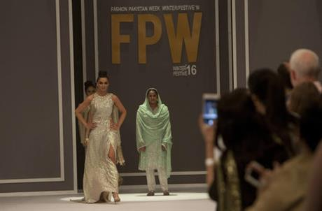 Pakistan's gang rape victim Mukhtar Mai, center right, walks with models during a fashion show in Karachi, Pakistan, Tuesday, Nov. 1, 2016. Gang-raped and paraded naked 14 years ago, Mukhtar Mai walked on a ramp in Pakistan fashion week on Tuesday. A red-carpet reception accorded in Pakistani southern city of Karachi by country's elite fashionista is her debut appearance, which she says she's doing as a symbol of courage for womenfolk.