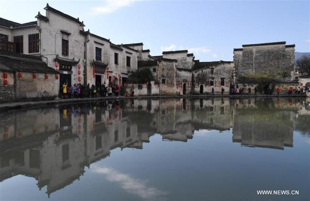 People visit the Yuezhao, or Moon Pool, at Hongcun, an ancient village in Yixian County in Huangshan City, east China's Anhui Province, Nov. 26, 2016
