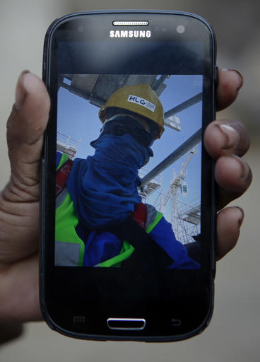 "In this Wednesday, Nov. 30, 2016, Saro Kumari Mandal, 26, holds a mobile phone displaying a selfie her husband Balkisun Mandal Khatwe had taken in Qatar in his yellow work hardhat and protective sunglasses, at her village in Belhi, Saptari District of Nepal. Saro had chatted with Balkisun through Facebook Messenger just the evening before his death. This is what happened, according to his supervisor: ""After work he went to dinner at 7 and bed at 10. In the morning we tried to wake him up but he didn't respond. We took the body to the hospital where they did an autopsy and said it was cardiac arrest."" About 10 percent of Nepal's 28 million residents are working abroad. They send back more than $6 billion a year, amounting to about 30 percent of the country's annual revenues. Only Tajikistan and Kyrgyzstan are more dependent on foreign earnings. (AP Photo/Niranjan Shrestha)"