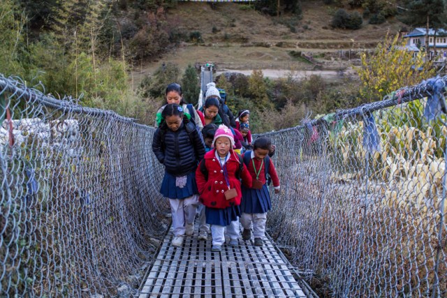 School children cross a suspension bridge over the Dhud Koshi River near Fakding village where the early warning system is installed.