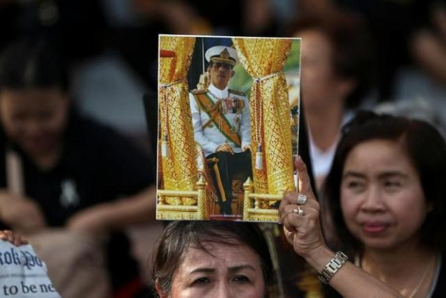 A woman holds up a picture of Thailand's Crown Prince Maha Vajiralongkorn before he arrives at the Grand Palace in Bangkok, Thailand, December 1, 2016. REUTERS/Athit Perawongmetha