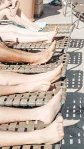 people's feet on sun loungers after having foot care.