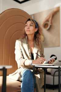 woman wearing blazer and blue denim jeans sitting on chair