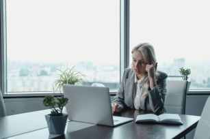woman in gray blazer sitting in front of gray laptop computer
