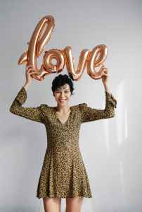 young cheerful woman showing sparkling balloon with word love