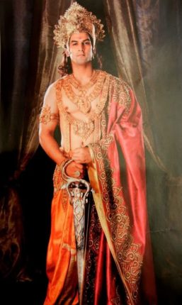 Pandu standing in royal attire