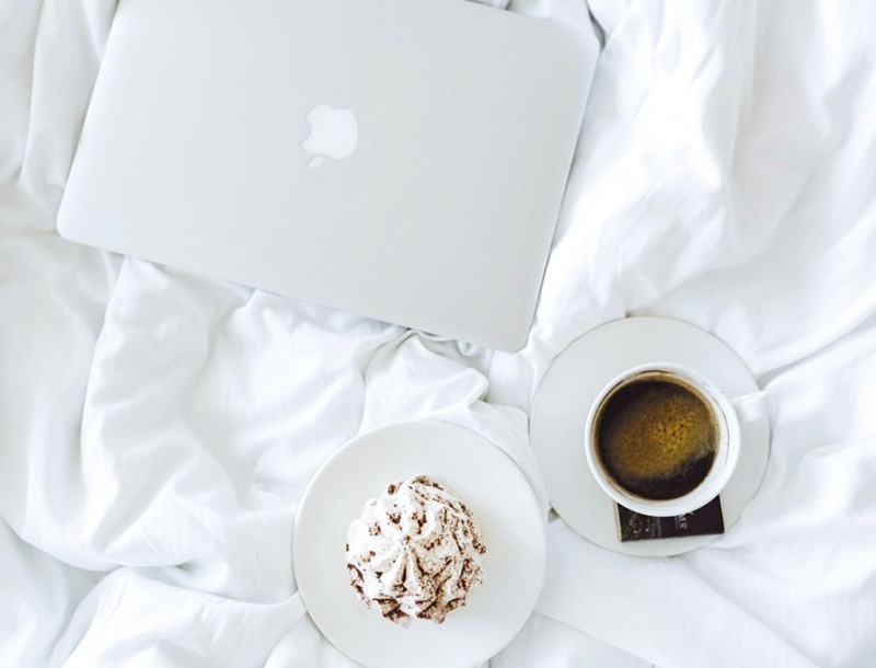 laptop and coffee on the bed