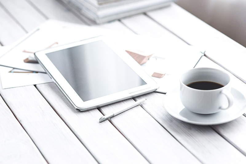 coffee on a desk with a tablet