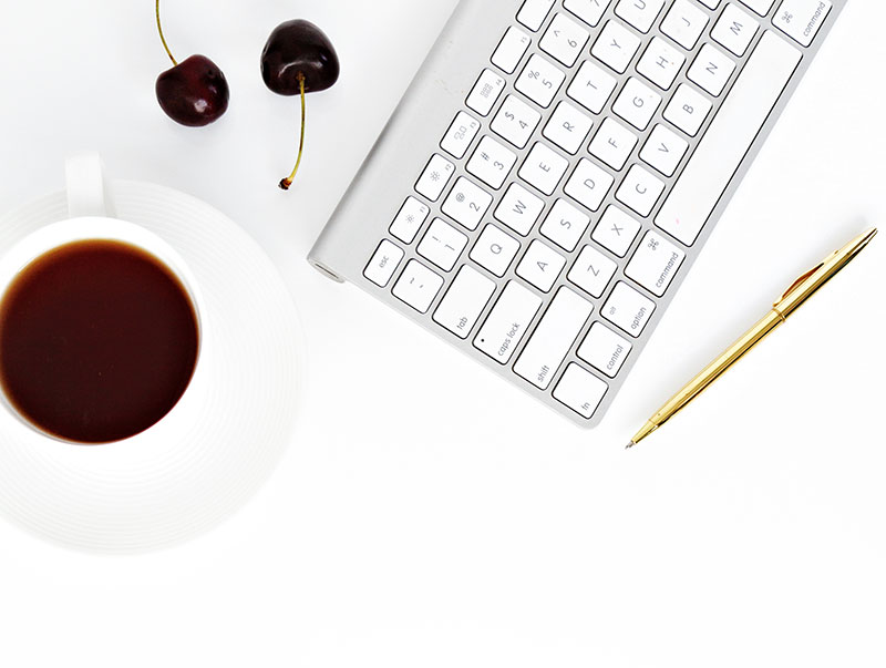 keyboard with tea and a pen