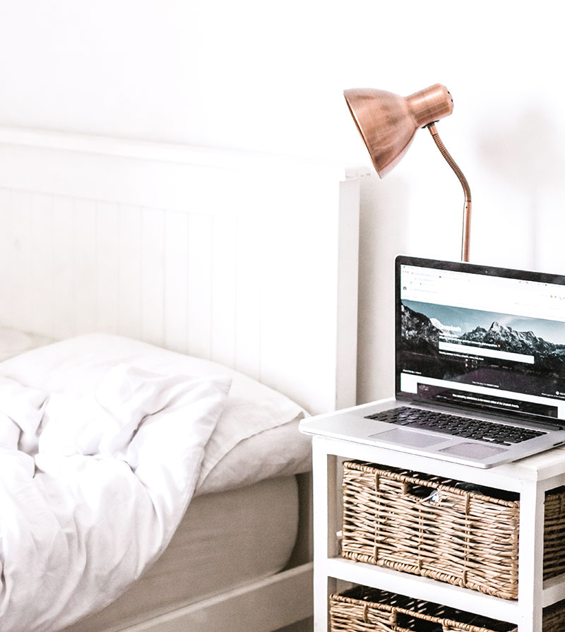 lamp and a laptop on a bedside stand