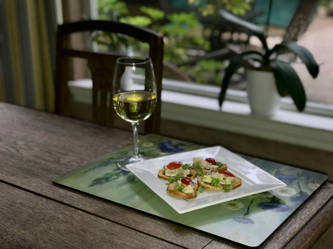 Crostini appetizer with a glass of white wine