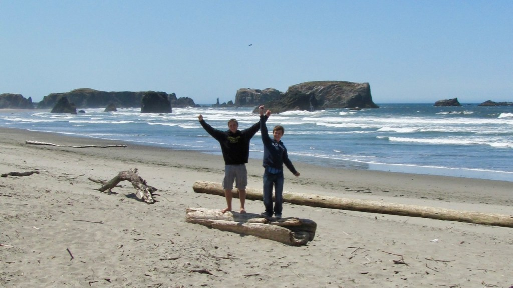 Teenage boys rejoicing on a rocky beach on the Northern Coast of Oregon.