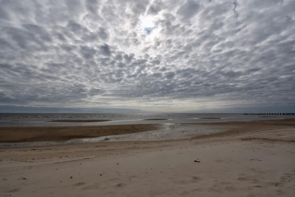 Beach at low tide and beautiful cloudy sky
