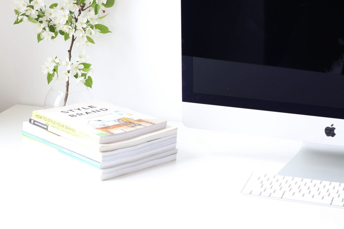 Mac on desk with books GLT Web Design