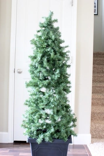Create a stunning evergreen tree topiary out of garland and tomato cages! They are perfect for porch displays this Christmas.
