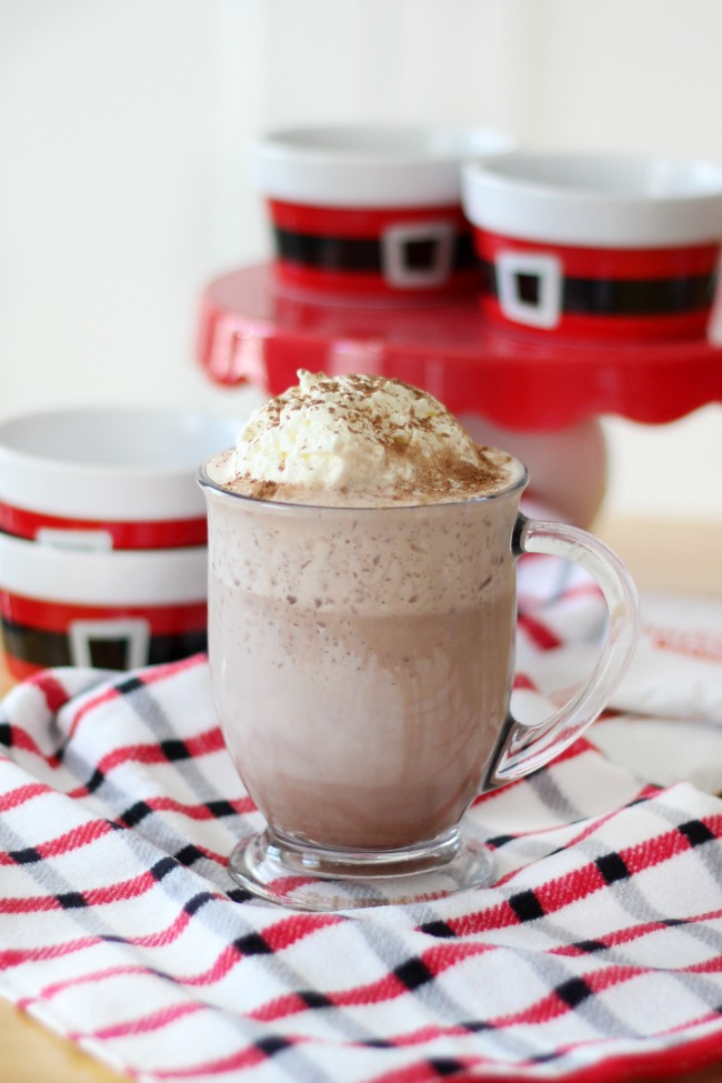 Hot cocoa, ice, and milk blend together for this delicious and creamy frozen hot cocoa! Top with whipped cream and cocoa powder.