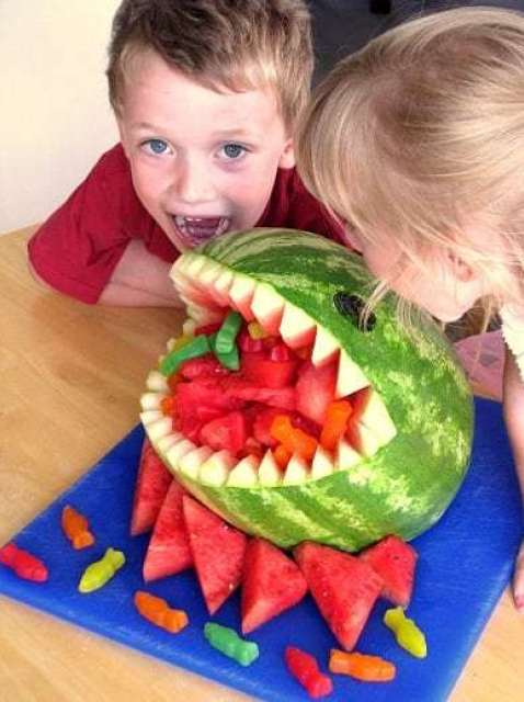 How to make a watermelon shark that is sure to be a hit at your next summer BBQ! Fill with fruit and gummy fish for a fun added detail!