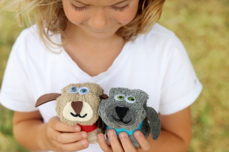 girl holding two no sew puppy wash cloths