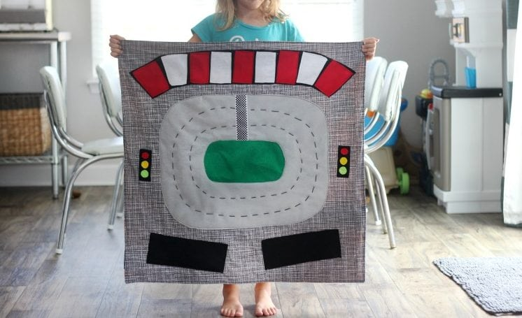 Make a race track play mat to inspire creative play in your home! This double sided mat is soft to sit on and folds up for easy storage. The perfect place to play with your favorite cars and trucks!