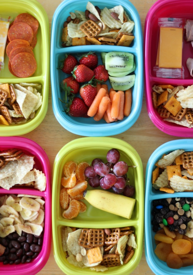 6 snack containers filled with a variety of sweet savory and fresh fruit snacks