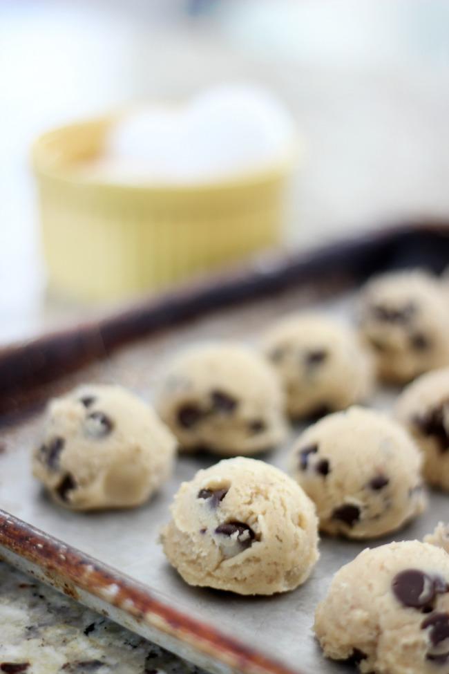 frozen cookie dough balls on baking sheet