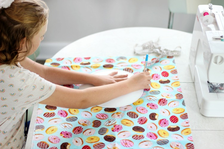 girl tracing around a plate on fabric